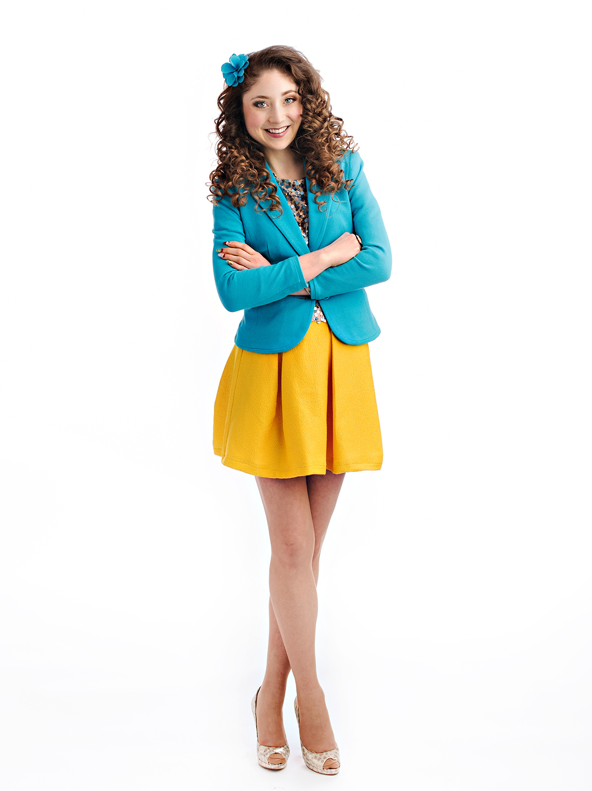 Kelly Lovell standing with her arms crossed in a power pose with a warm smile on her face and wearing blue and yellow blazar